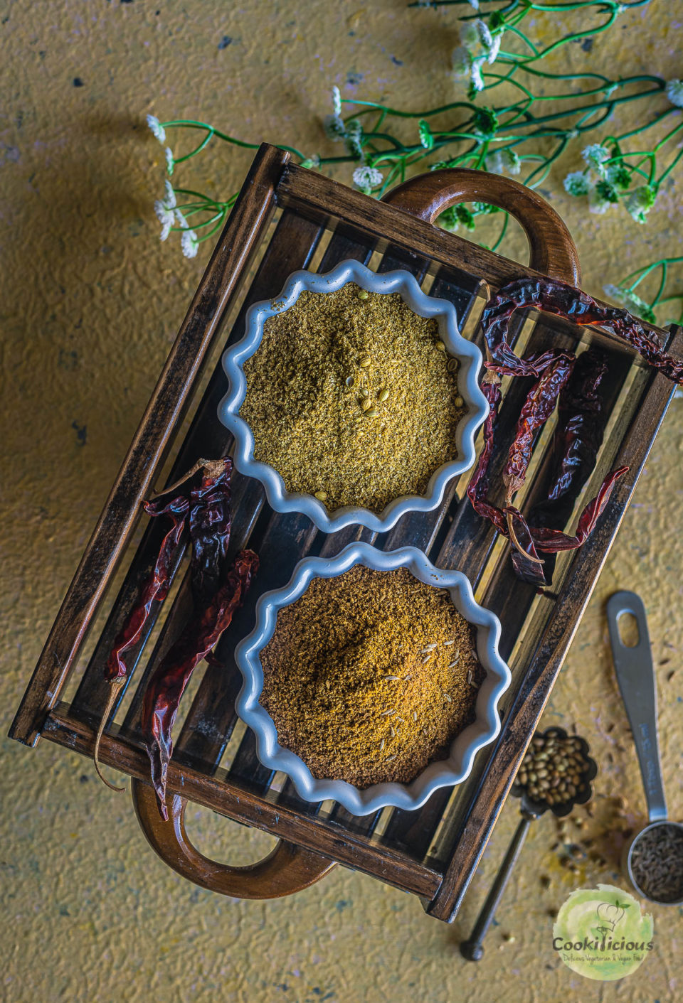 one bowl filled with cilantro powder and one bowl filled with ground cumin placed in a wooden tray