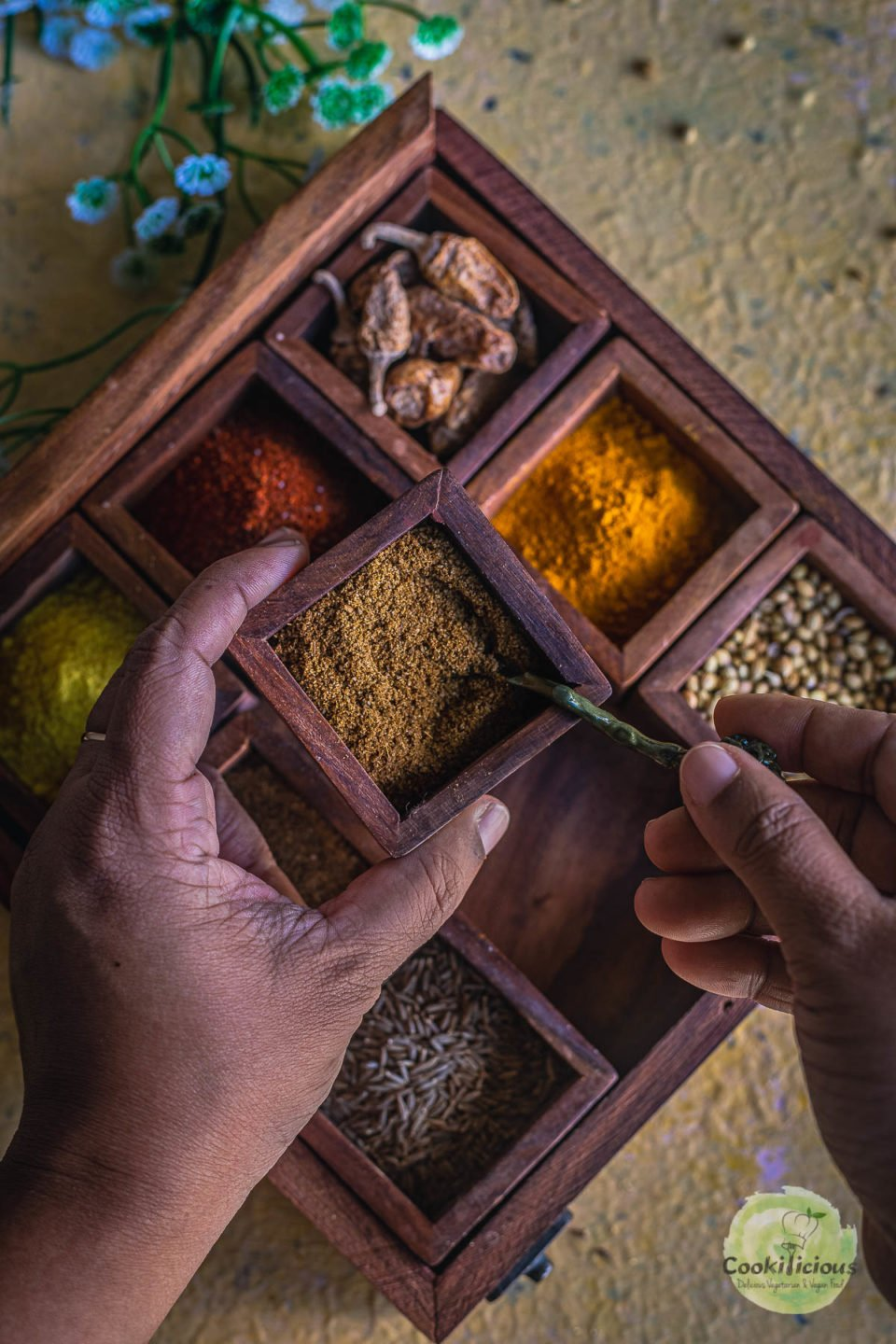 a set of hands putting a spoon into a spice box container which has ground cumin