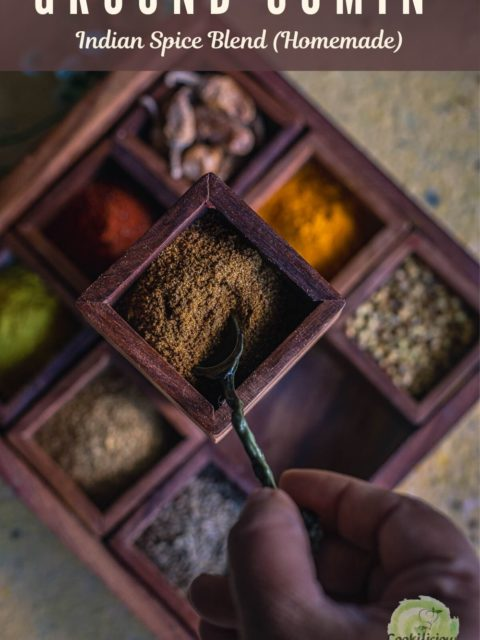 a hand putting a spoon into the spice box which has coriander cumin powder
