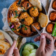 one hand holding the pan filled with Spicy Kofta Curry with Plant-Based Meatballs and the other digging in with a spoon