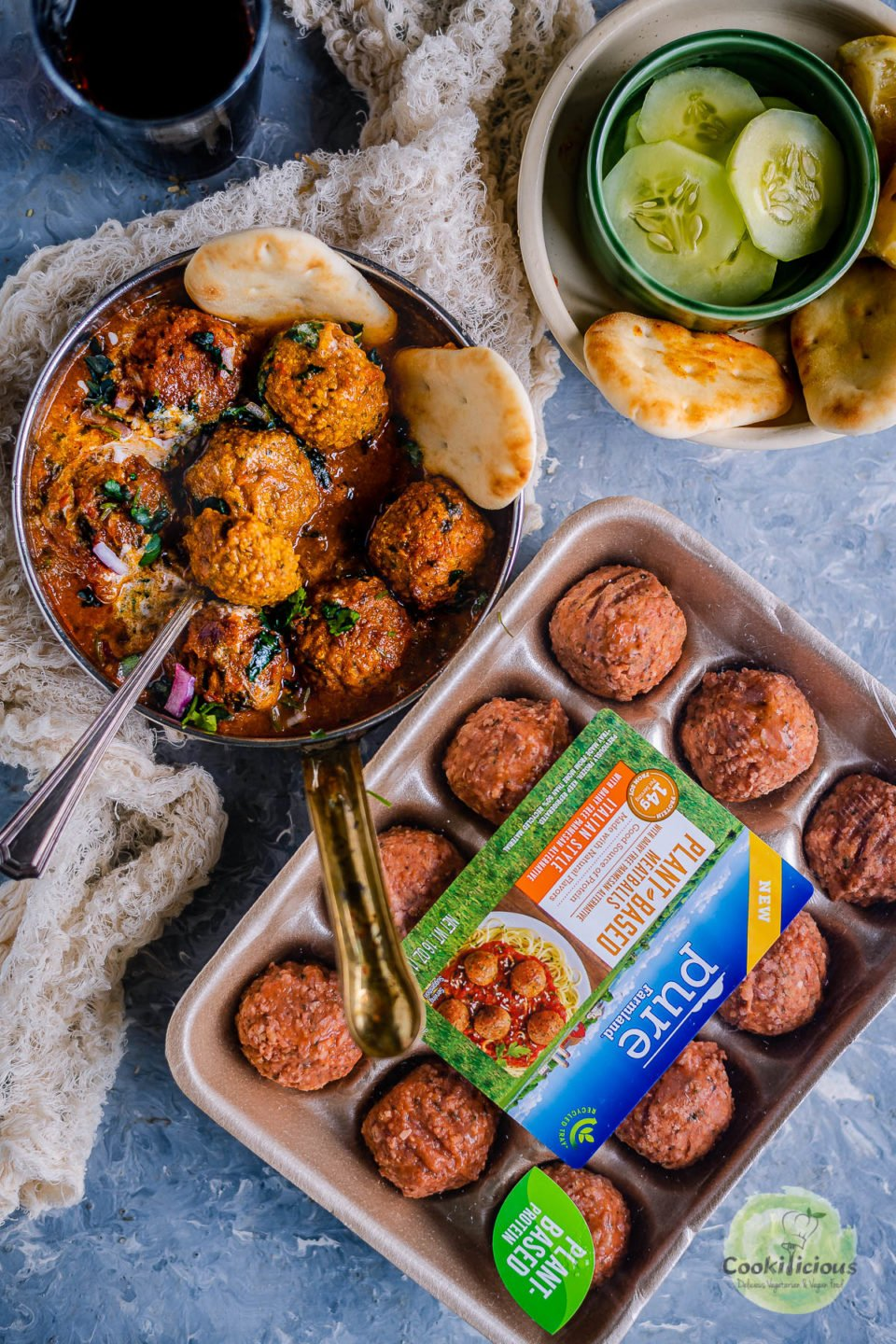 a pan of Spicy Kofta Curry with Plant-Based Meatballs with frozen meatballs on the side