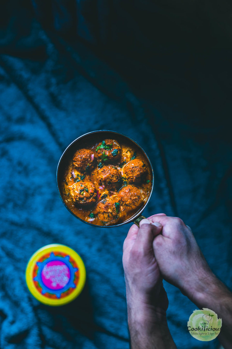 a set of hands holding a pan of Spicy Kofta Curry with Plant-Based Meatballs