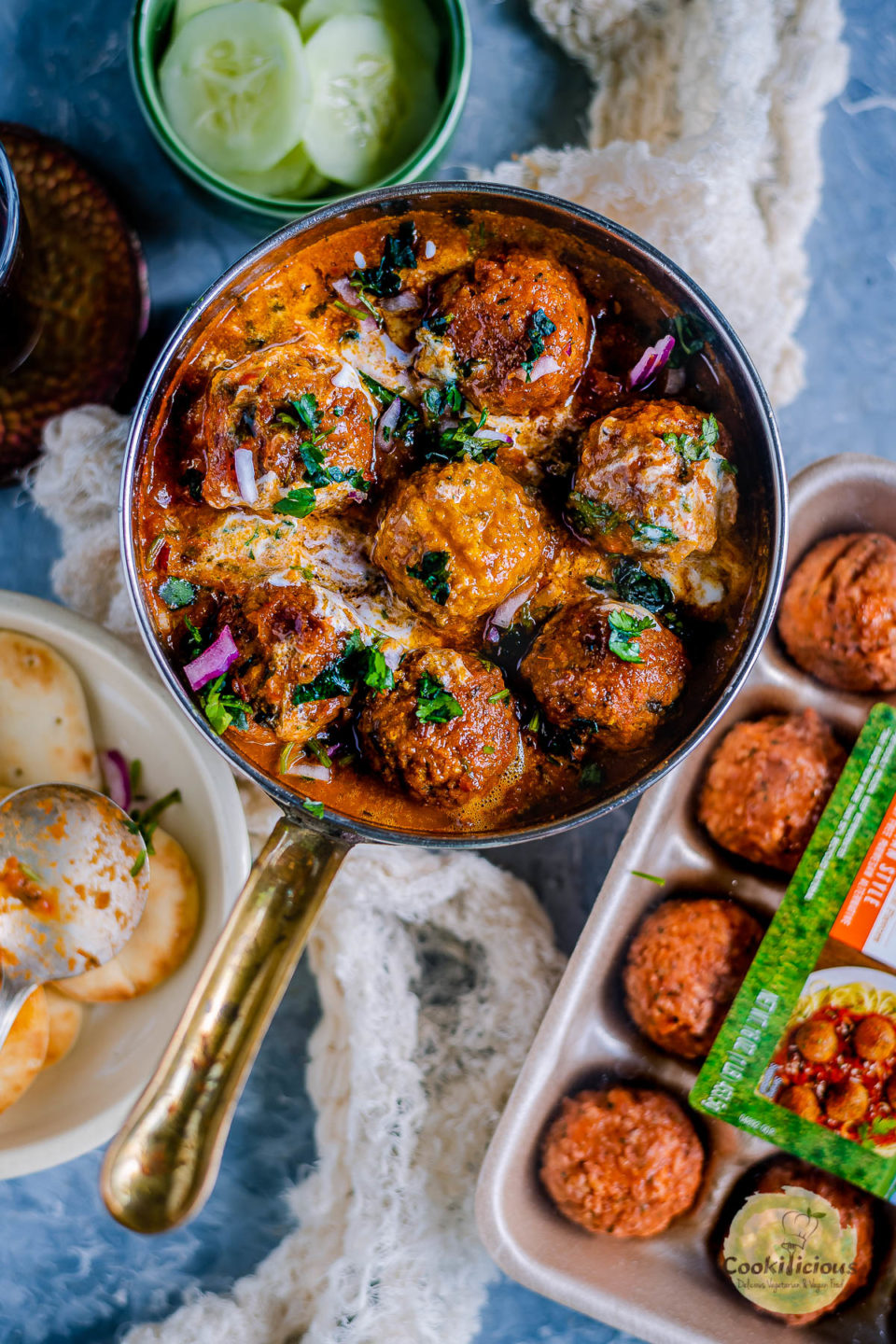 a round serving pan filled with Spicy Kofta Curry with Plant-Based Meatballs