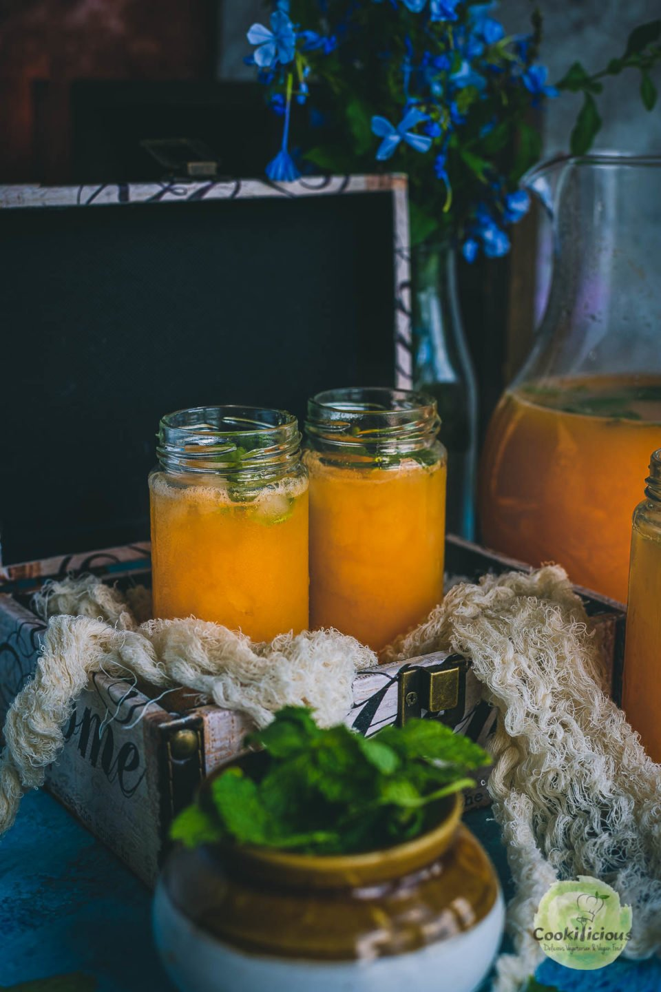 2 glasses filled with Organic Energy Drink With Carrots, Orange and Cantaloupe placed in a box