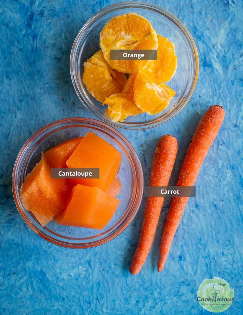 all the ingredients used to make Organic Energy Drink With Carrots, Orange and Cantaloupe placed in a tray with labels on them