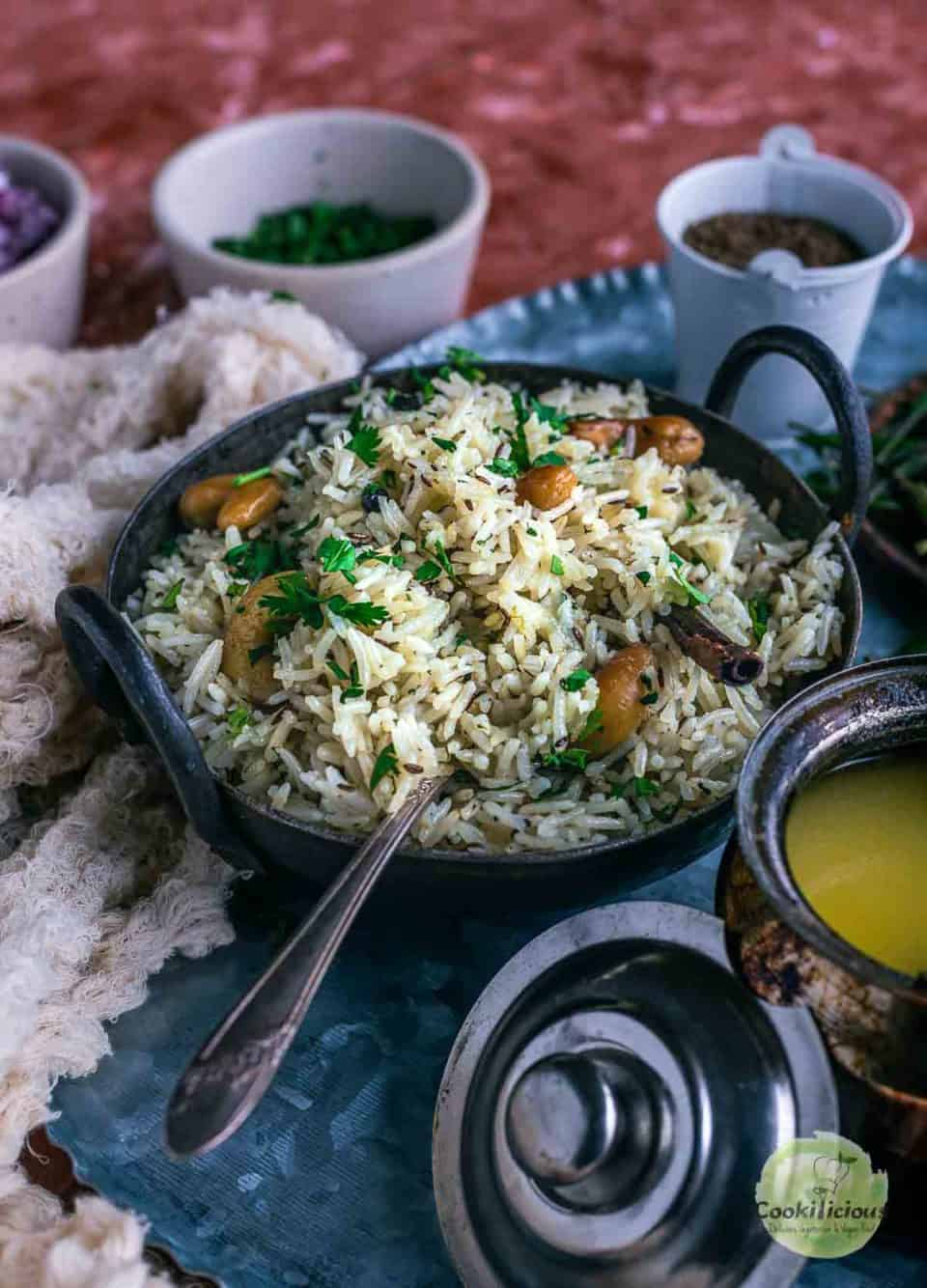 a small round wok filled with Jeera rice with a spoon in it
