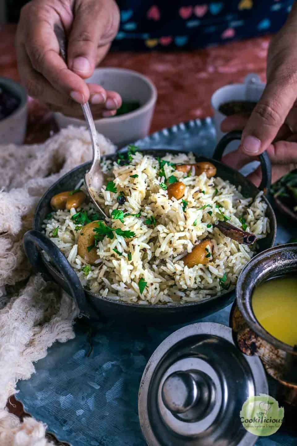 one hand holding a small kadai filled with jeera rice while the other hand is digging in with a spoon