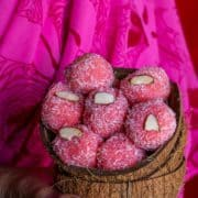 a lady holding coconut shells filled with Instant Rose flavored Coconut Ladoo