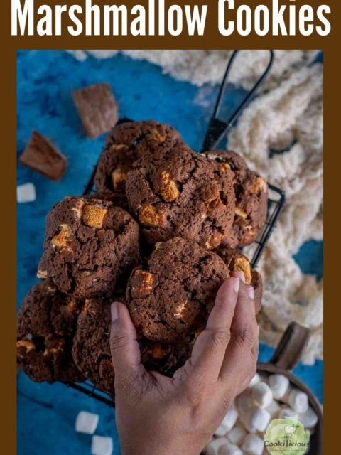 a hand reaching out to pick up one Vegan Marshmallow Chocolate Cookie with text at the top