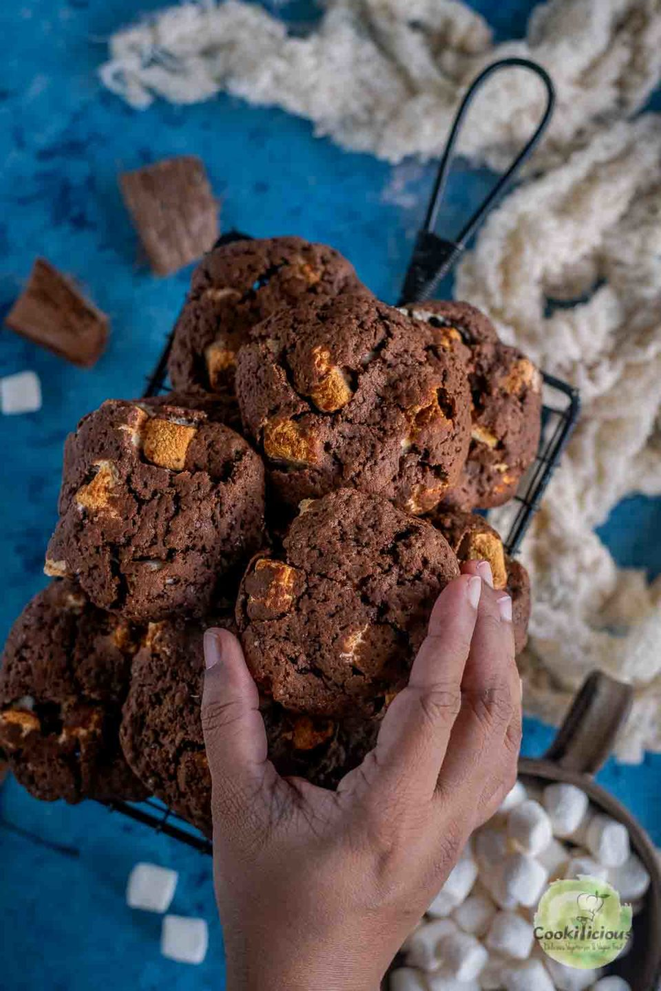 a hand reaching out to pick up one Vegan Marshmallow Chocolate Cookie