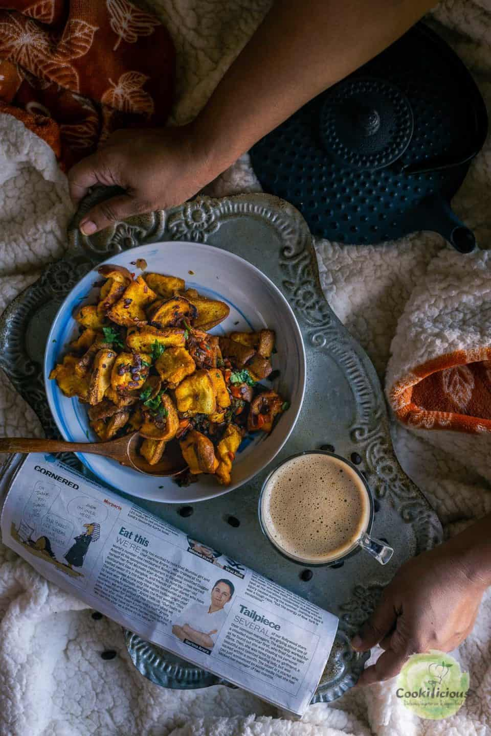 a set of hands placing a tray with coffee, bread upma and newspaper on the bed