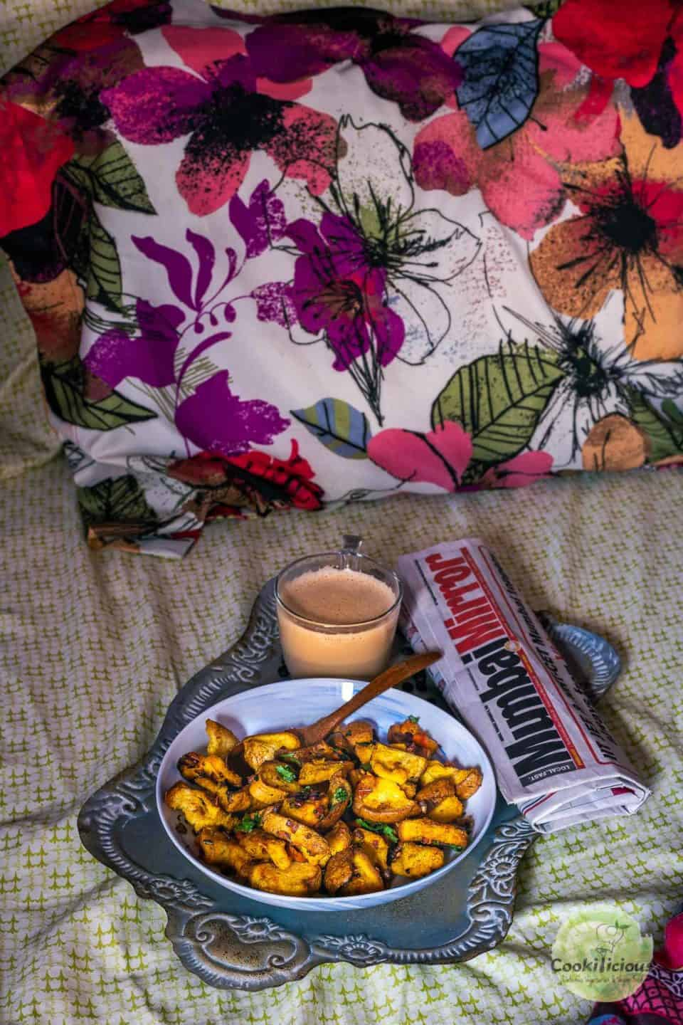 a tray with coffee, newspaper and a plate of bread upma placed on a bed