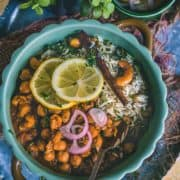 a round bowl filled with Vegan Chana Masala with a spoon in it