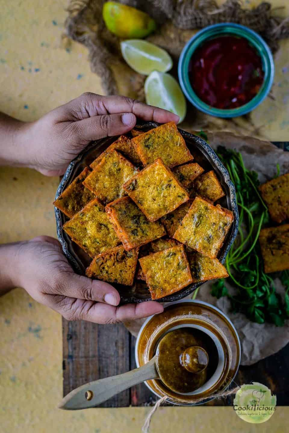a set of hands holding a platter full of fried Vegan Cabbage Fritters