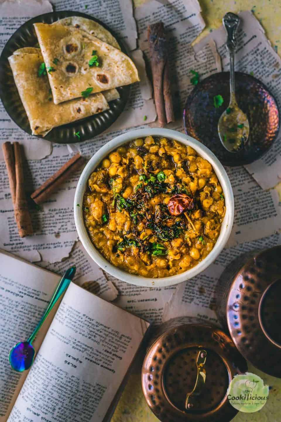 flat lay image of Yellow Peas Curry Chili  in a bowl with a plate full of chapati on the side