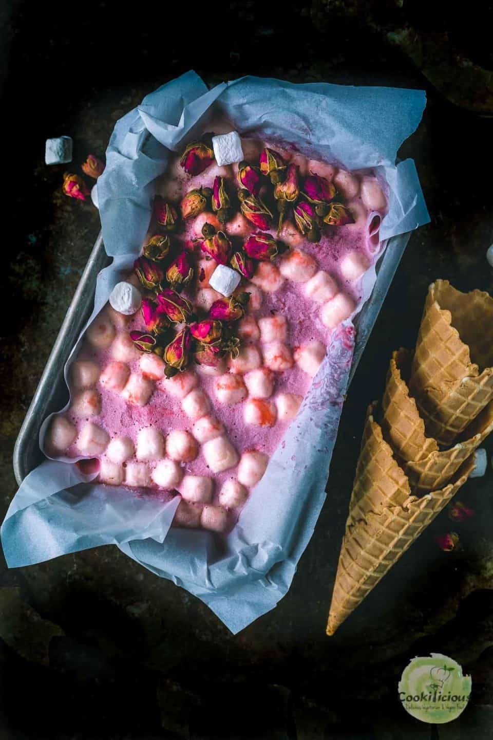 strawberry marshmallow ice cream set in a loaf pan with some cones next to it