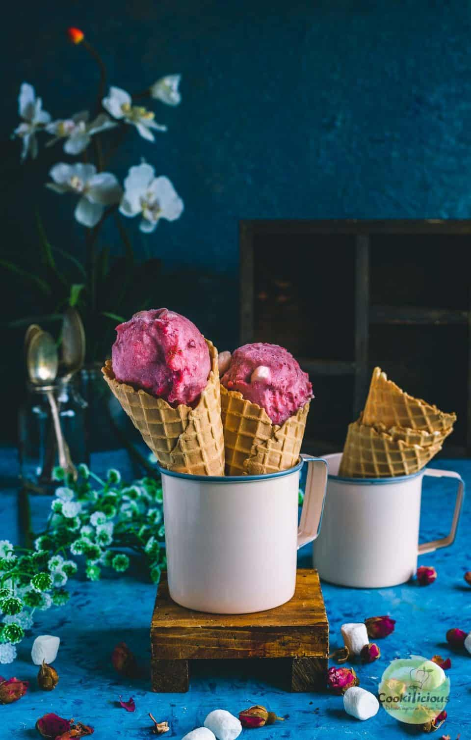 2 strawberry marshmallow ice cream cones placed in a mug