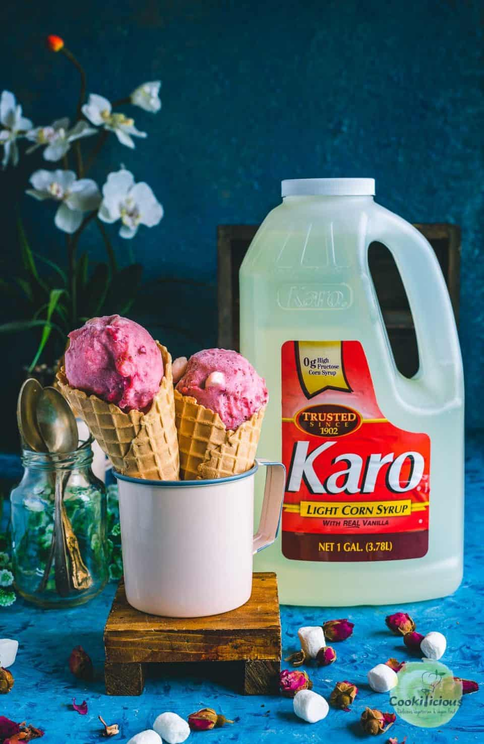 2 strawberry marshmallow ice cream cones placed in a mug and a gallon on Karo corn Syrup placed next to it