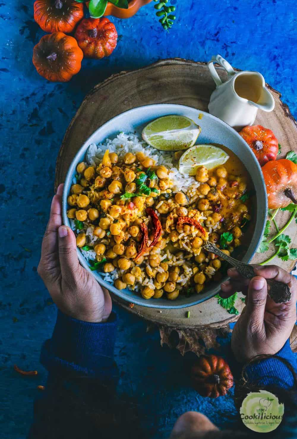 one hand holding the bowl while the other hand is holding a spoon and digging into the bowl filled with Instant Pot Butternut Squash Chickpea vegan Thai Curry