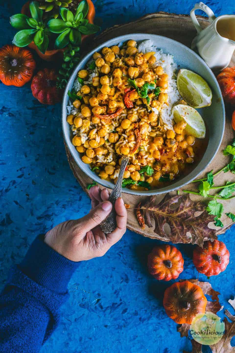 a hand holding a spoon and digging into a bowl of Instant Pot Butternut Squash Chickpea vegan Thai Curry