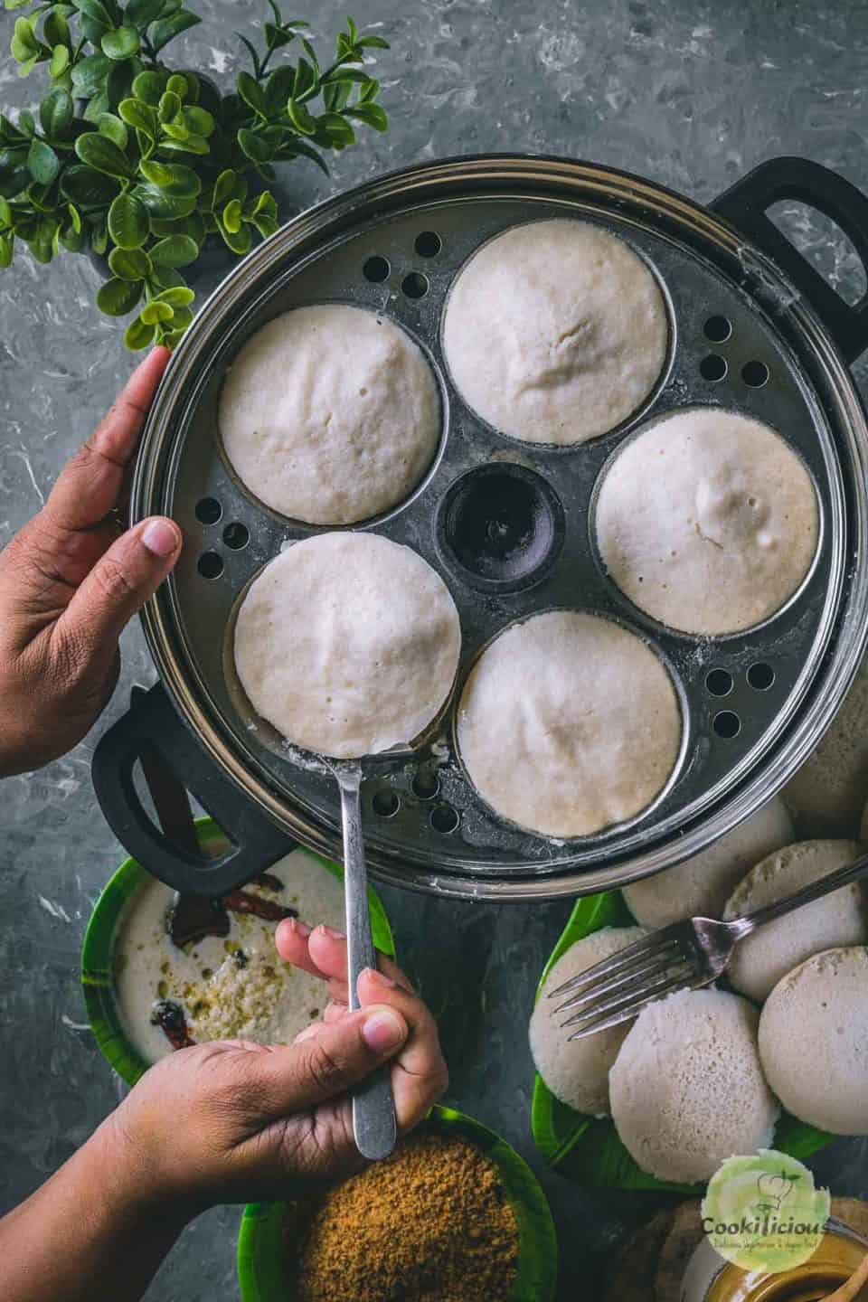 a pair of hands removing idlis from the cooker using a spoon