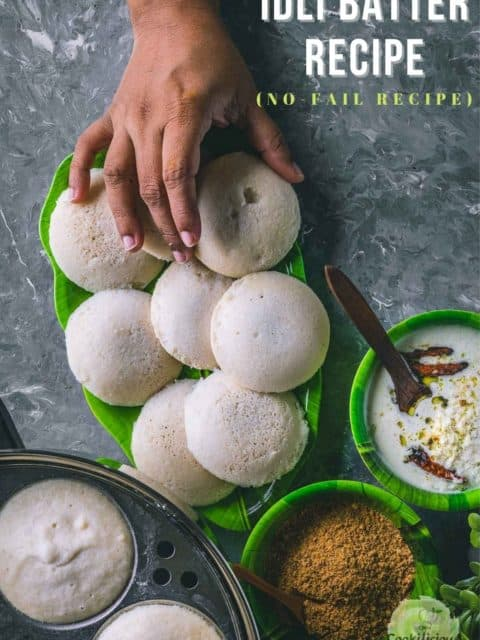 a plate full of white steamed idlis and one hand reaching out to pick one and text at the top