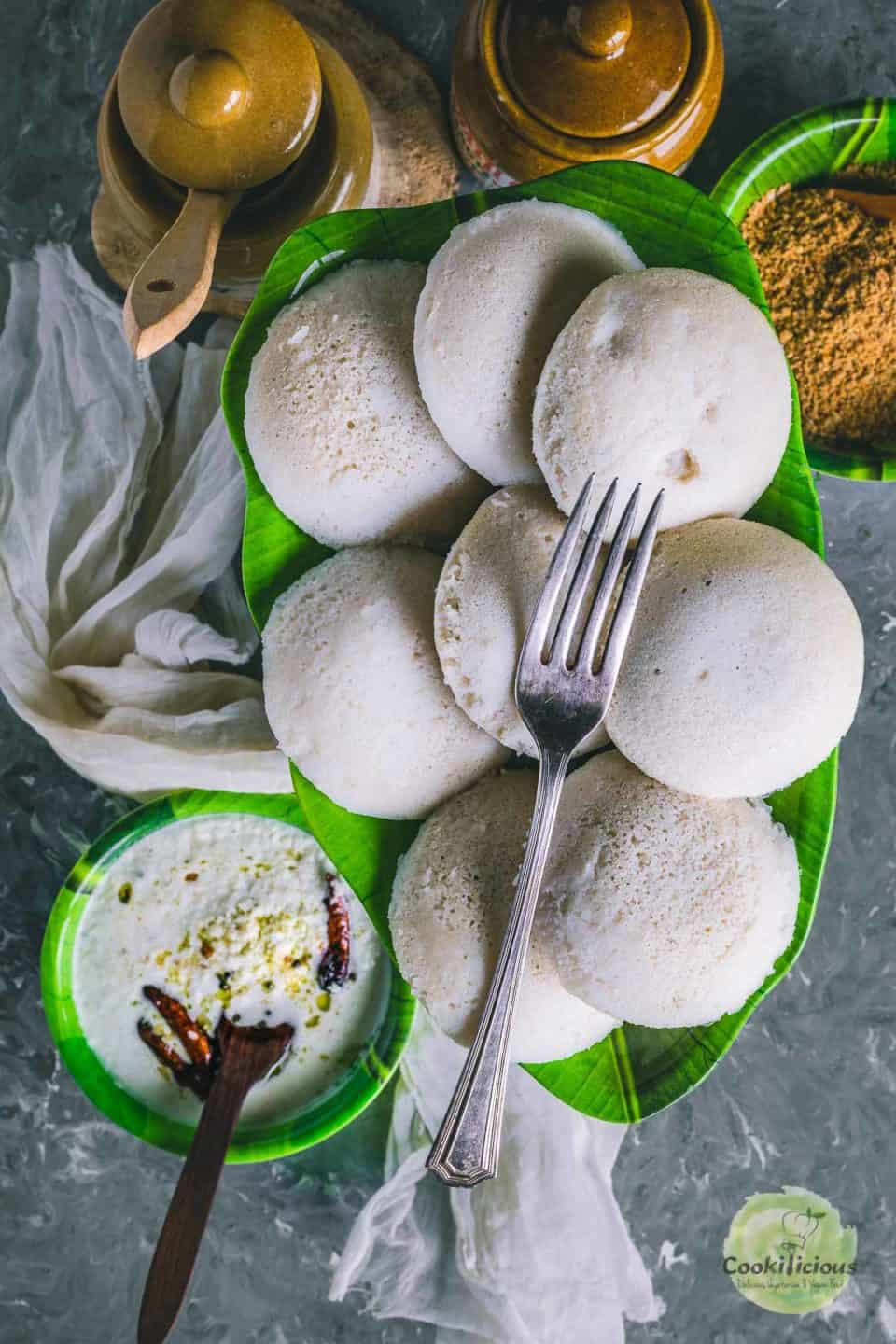 a plate full of idlis with one fork on top