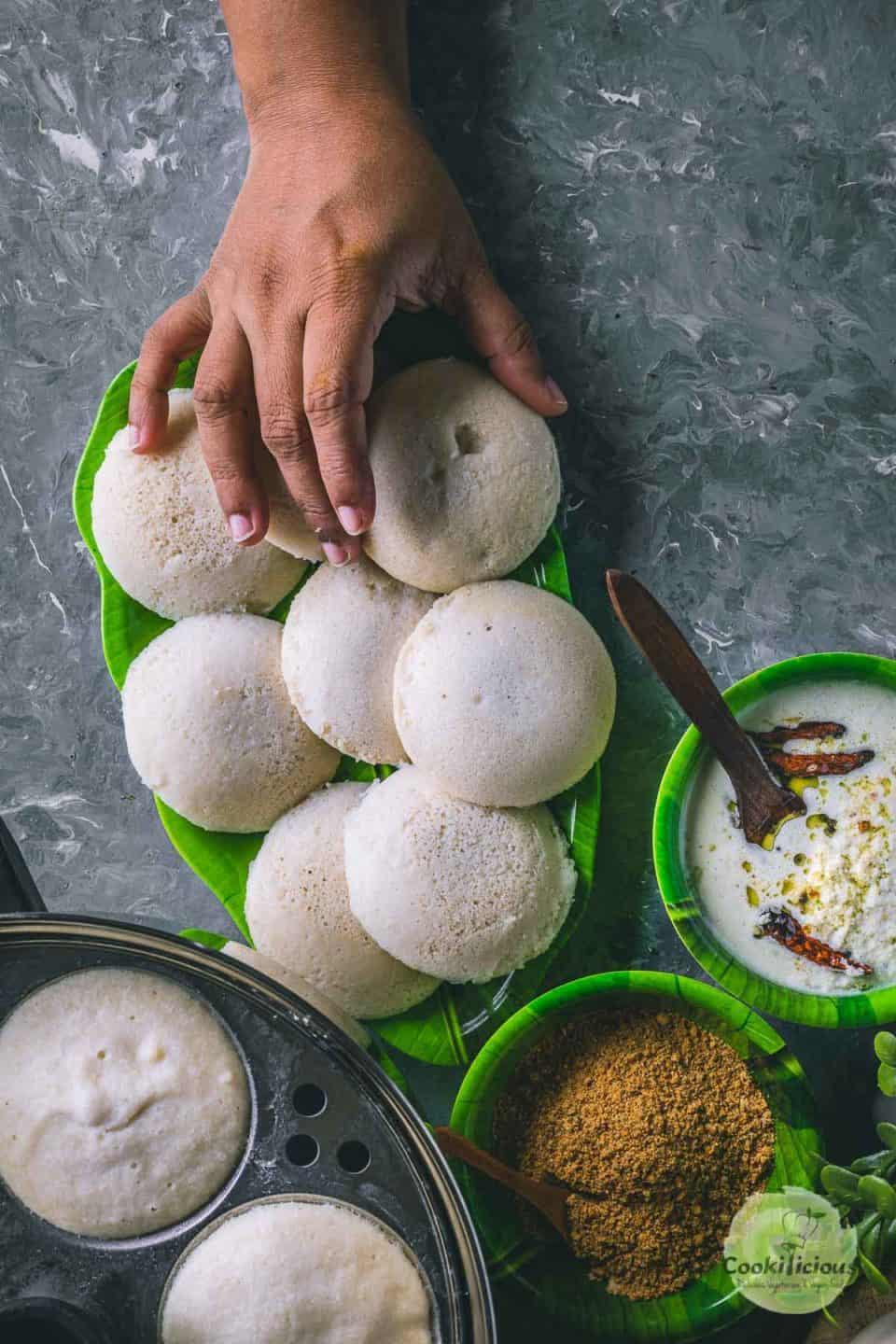 a plate full of white steamed idlis and one hand reaching out to pick one