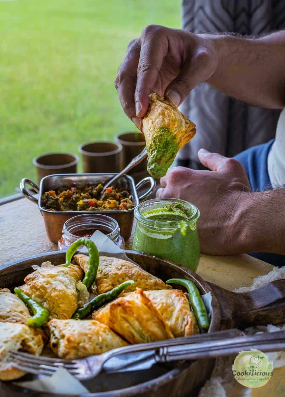 a man sitting at the dining table and dunking a Vegetable Puff Pastry Samosa into a bowl of green chutney