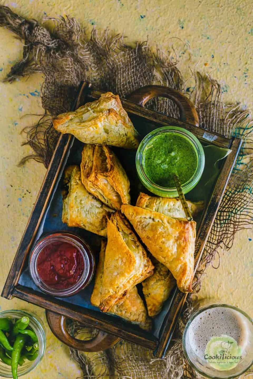 Vegetable Puff Pastry Samosa served in a tray with ketchup and chutney on the side
