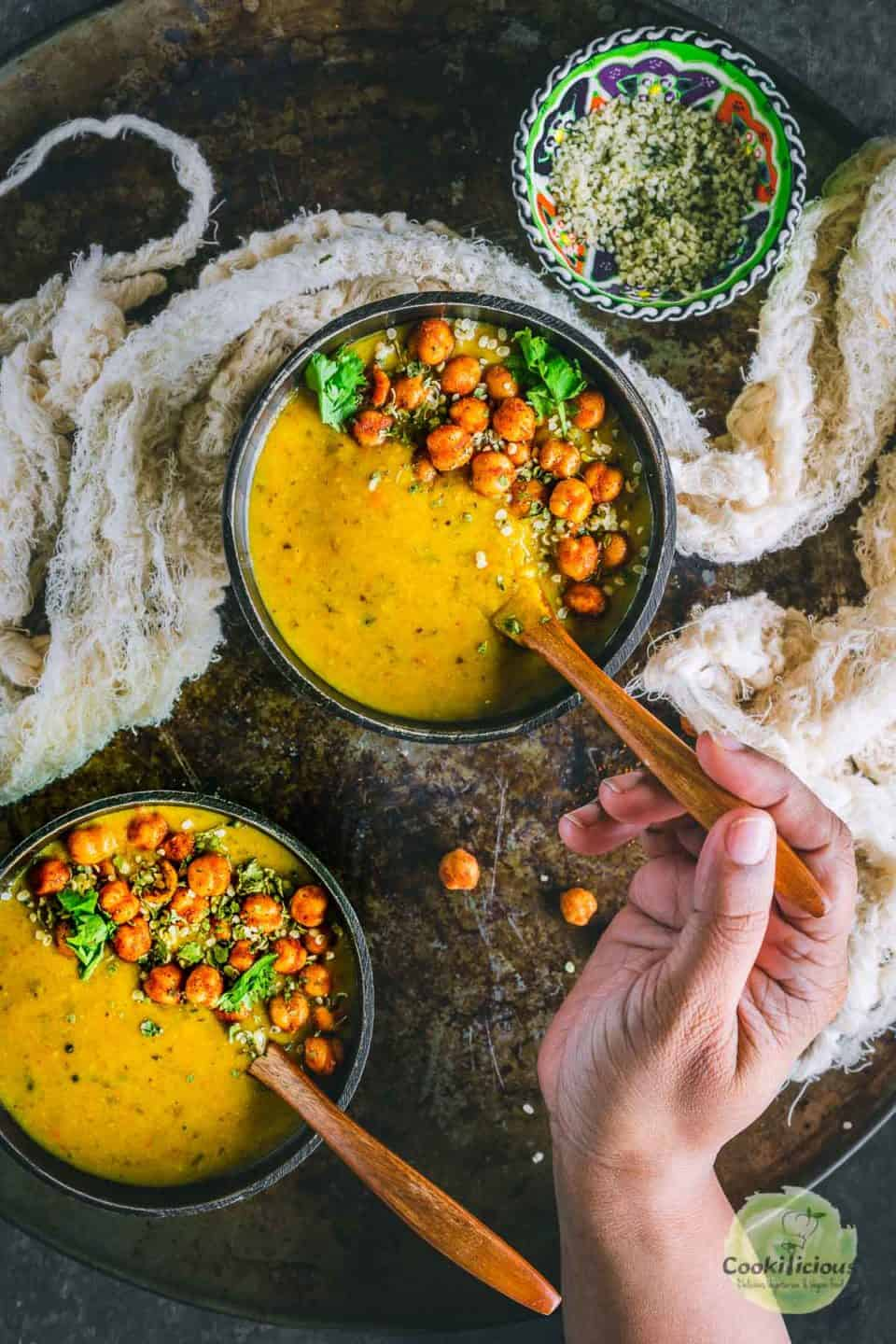 a hand holding a spoon and digging into a bowl of Vegan Lentil Soup | Indian Dal Shorba