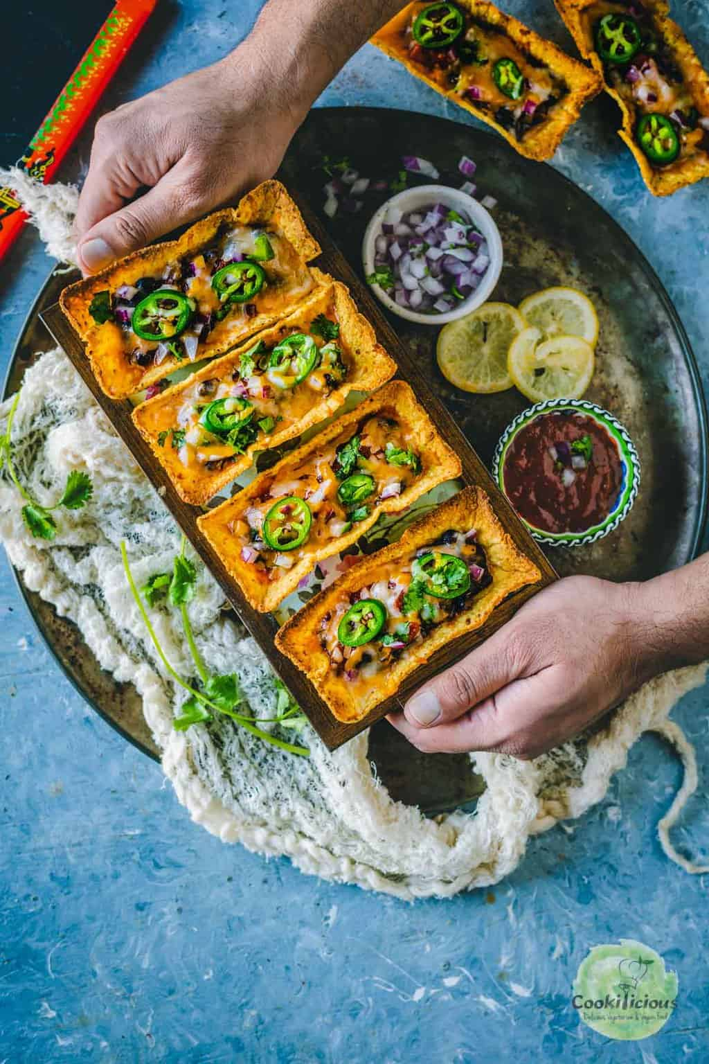 a set of hands serving a platter filled with Instant Pot Black Beans Taco Boats