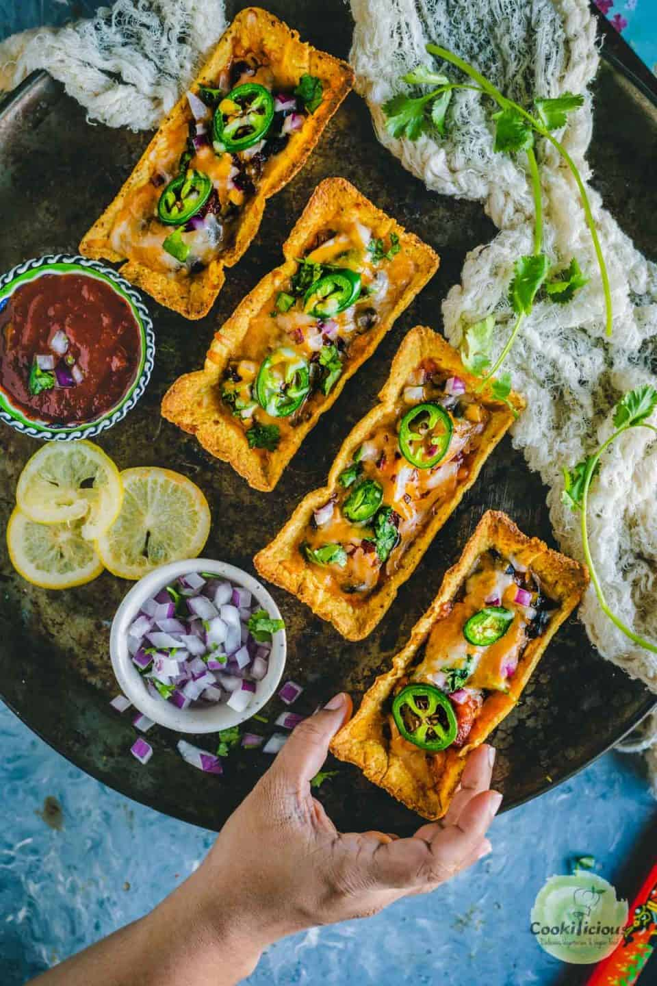 one hand reaching out to pick one of the Instant Pot Black Beans Taco Boats