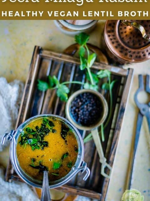 Jeera Milagu Rasam served in a bucket and placed on a wooden tray and text at the top
