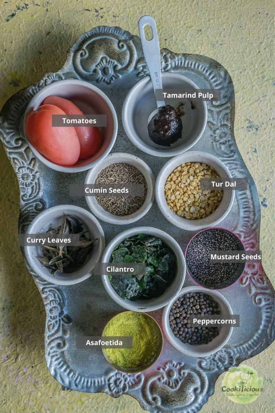 all the ingredients needed to make Jeera Milagu Rasam placed on a tray with labels on them