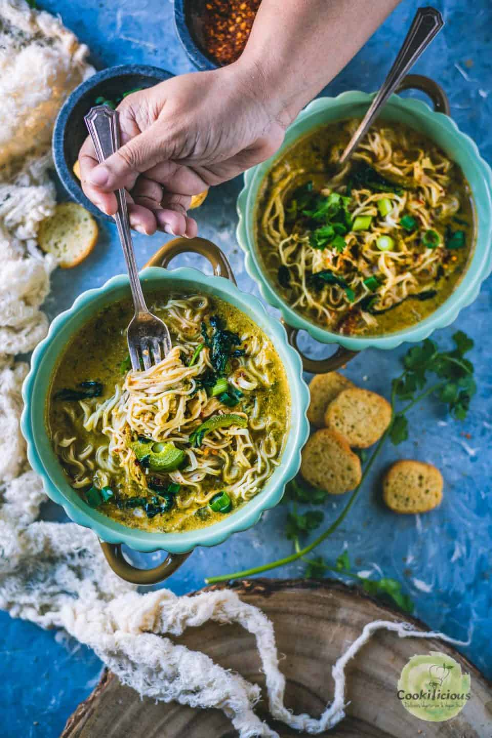a hand digging into a bowl of Vegan Thai Curry Noodles Soup with a spoon