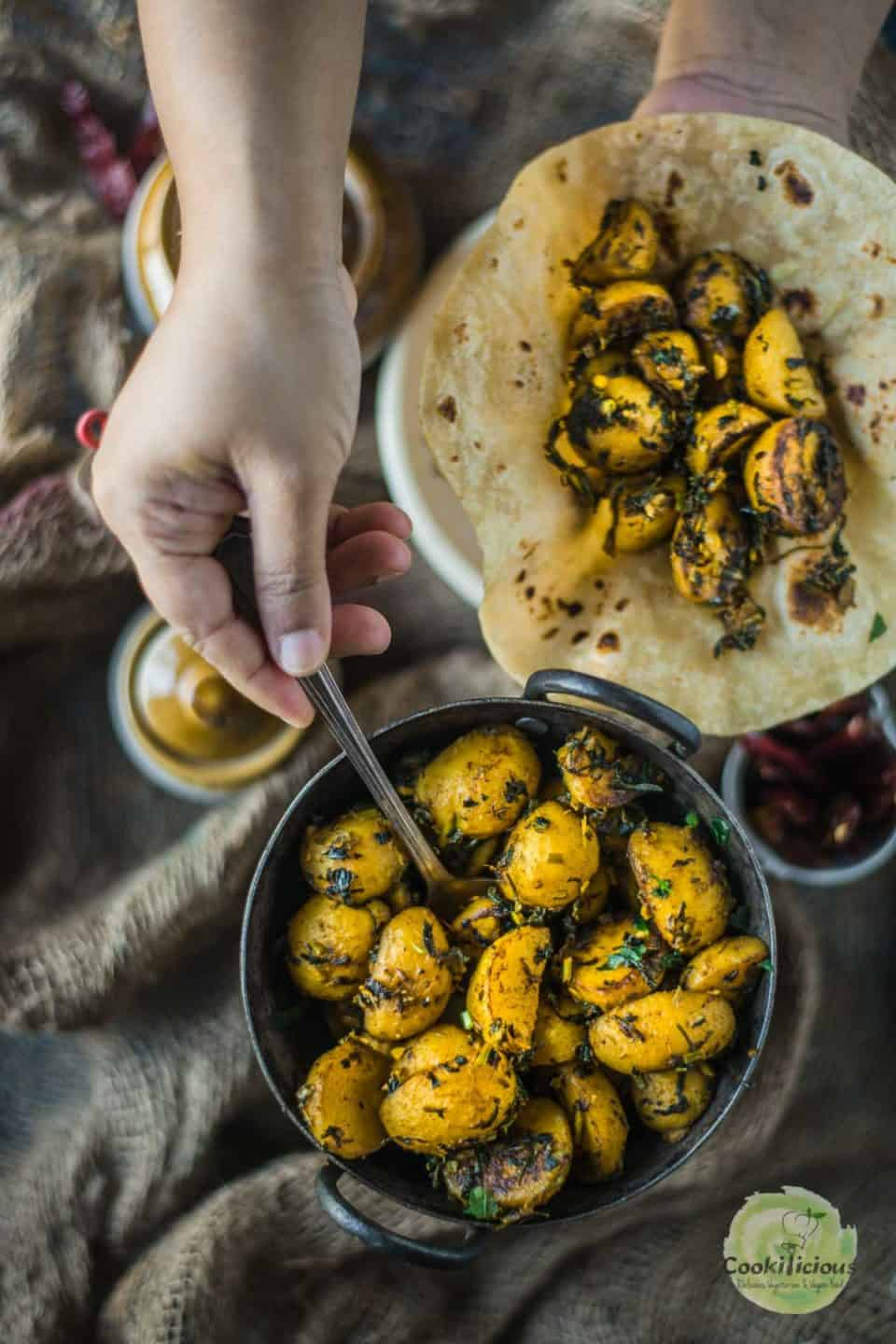 a hand digging into a bowl of Aloo Methi using a spoon