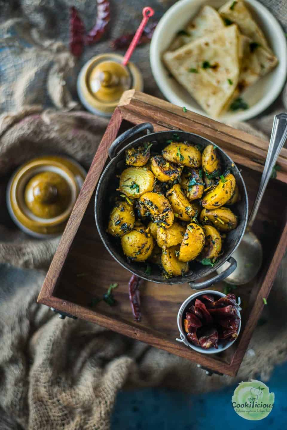 Aloo Methi served in a kadai and placed on a wooden tray