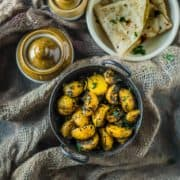 Aloo Methi served with chapati and pickle jars on the side