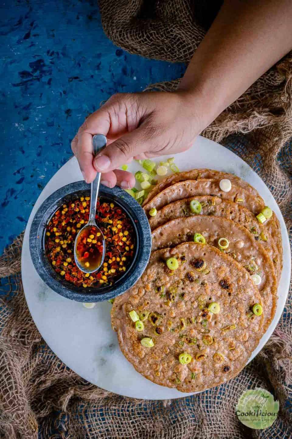 Chinese Scallion Pancakes served in a platter with one hand putting a spoon into the dipping sauce next to it