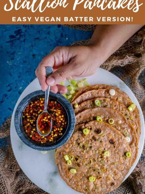Chinese Scallion Pancakes served in a platter with one hand putting a spoon into the dipping sauce next to it and text at the top and bottom