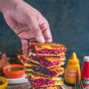 a hand picking up one Savory French Toast from a stack