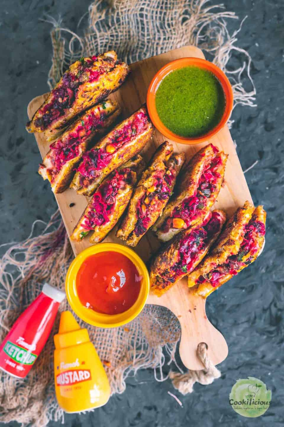 Savory French Toast slices placed on a wooden board with a bowl of ketchup and chutney