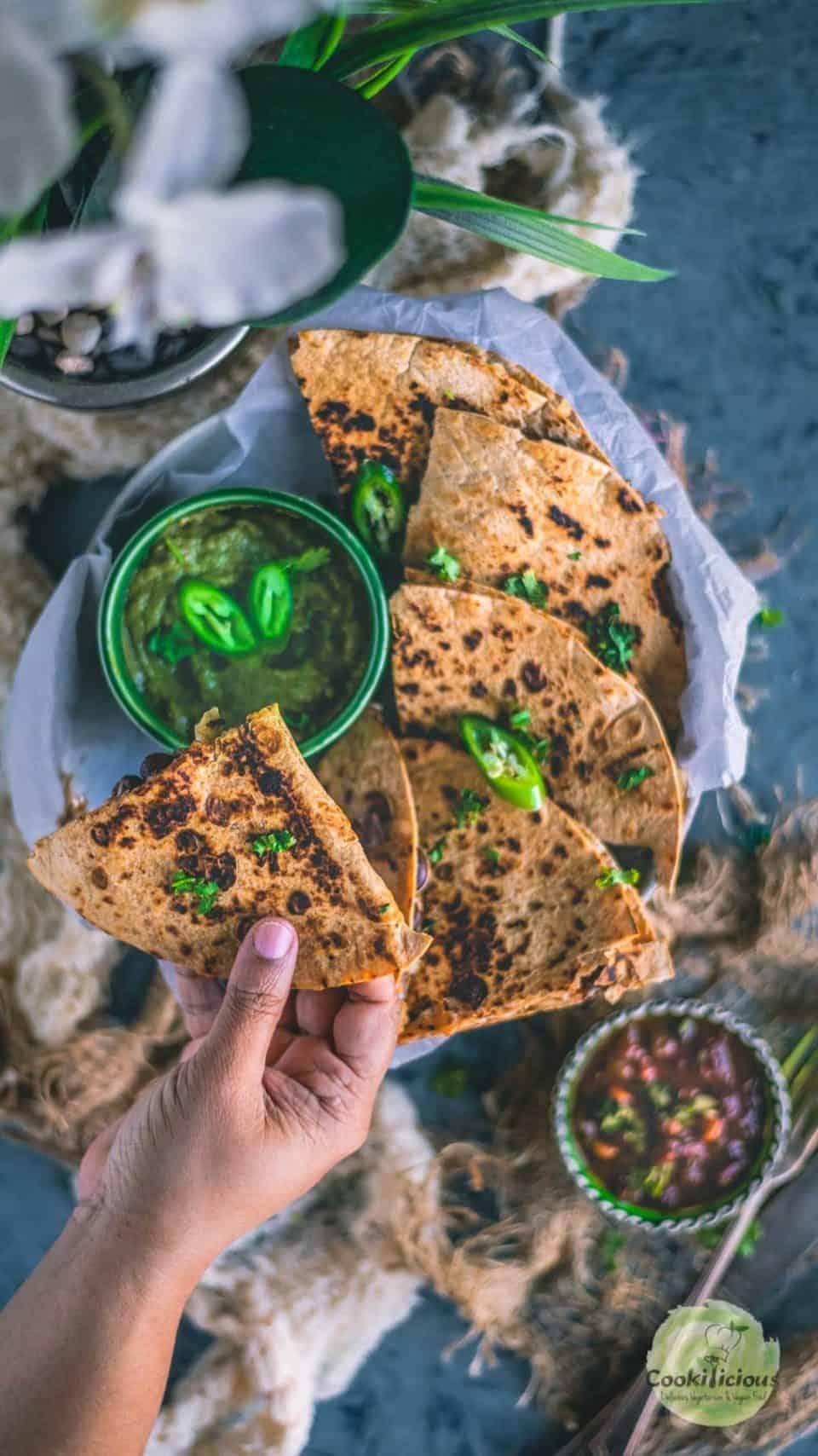 one hand holding a wedge of Tandoori Cheese Quesadilla