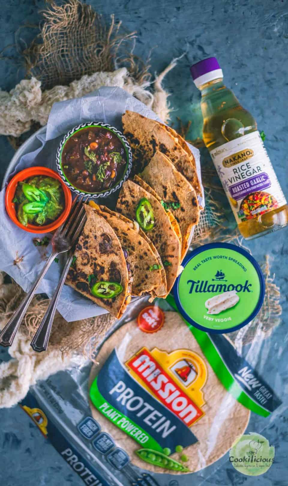 Tandoori Cheese Quesadilla served in a plate with a bottle of rice vinegar, packet of tortillas and cream cheese spread placed around it