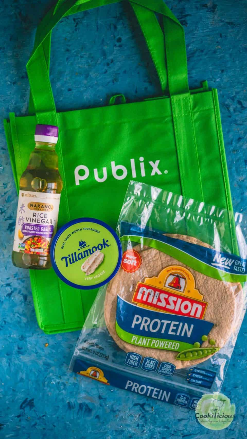 a Publix shopping bag with a packet of tortillas, rice vinegar and cream cheese spread around it