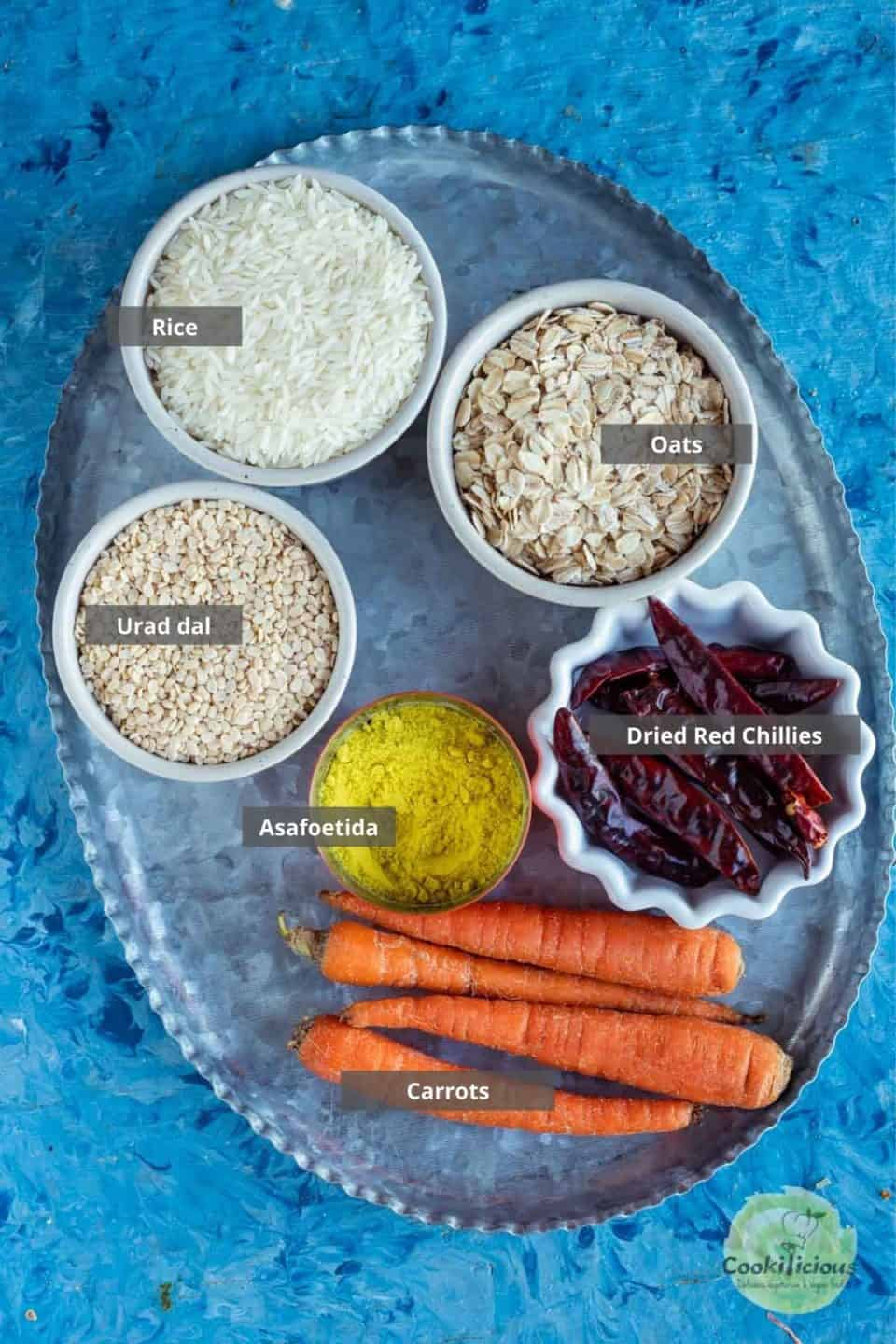 all the ingredients needed to make Oats Carrot Dosa placed in a tray with labels on them