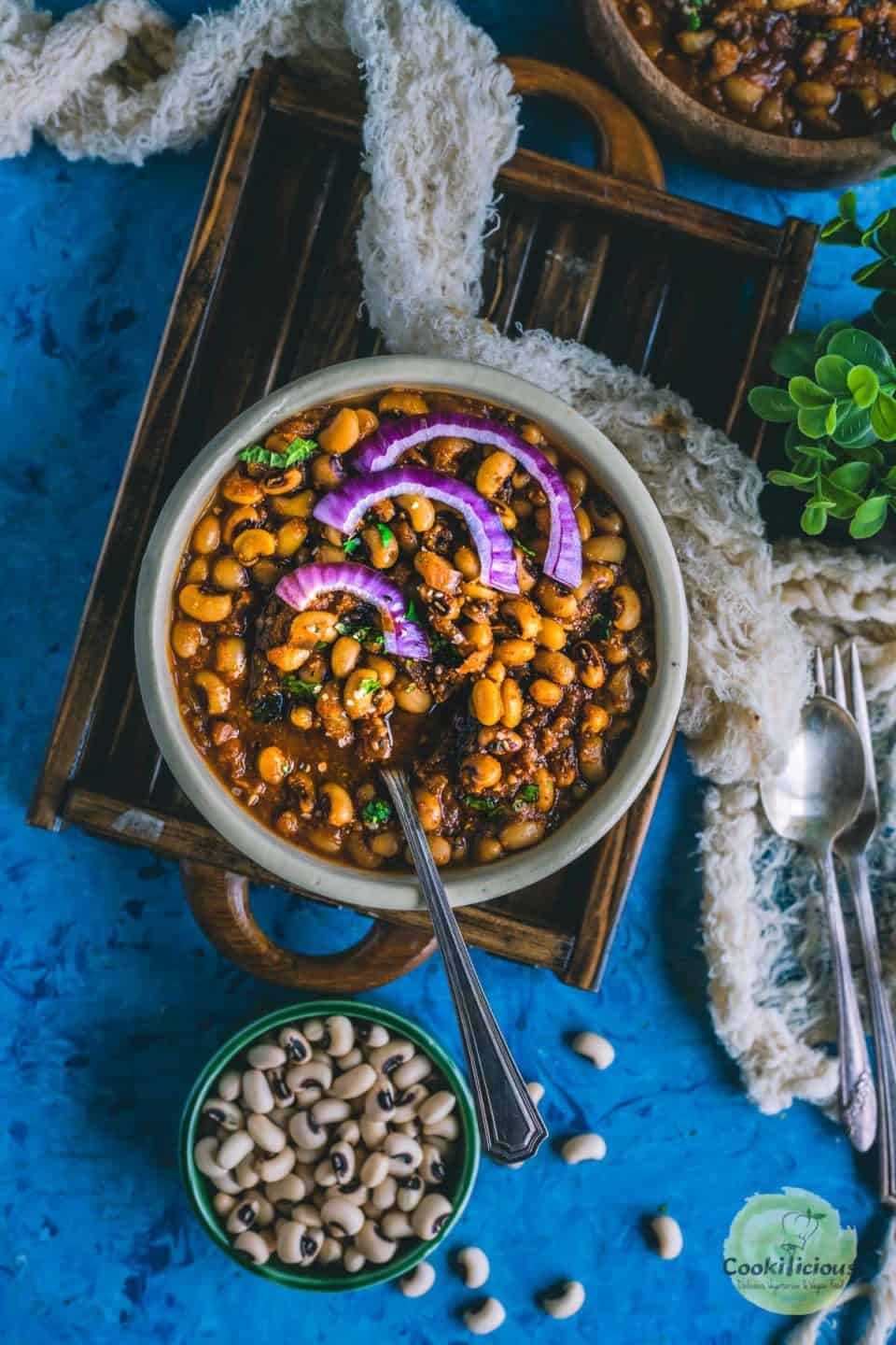 Chettinad Black Eyed Peas Curry  served in a round bowl with a spoon in it