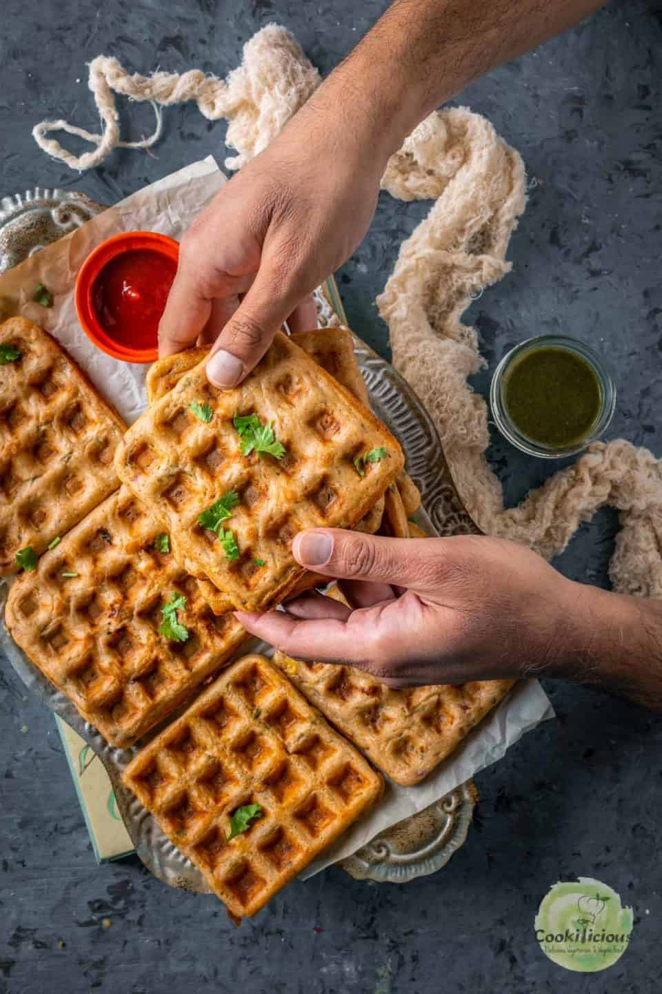 a set of hands holding one Vegan Savory Dosa Waffle