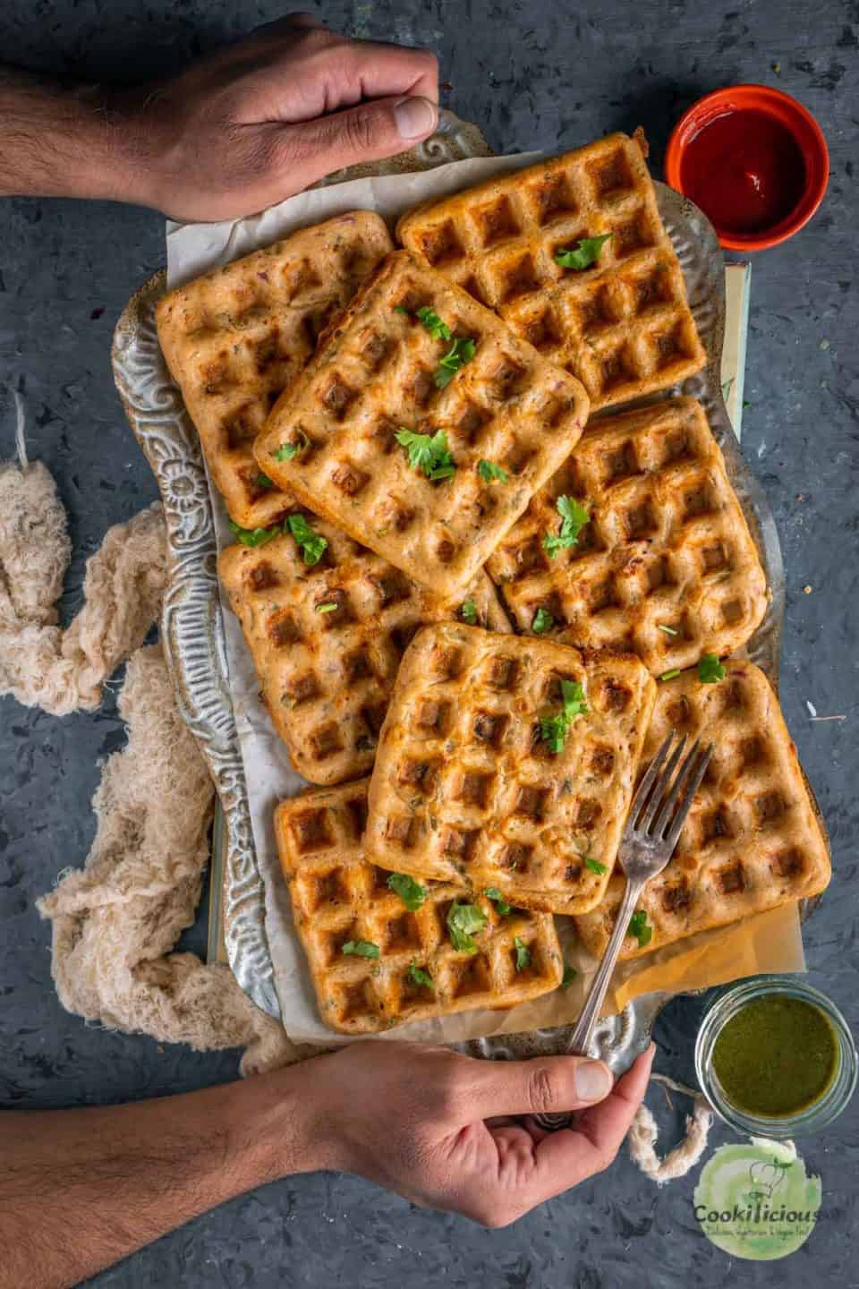 a set of hands serving a tray filled with Vegan Savory Dosa Waffles